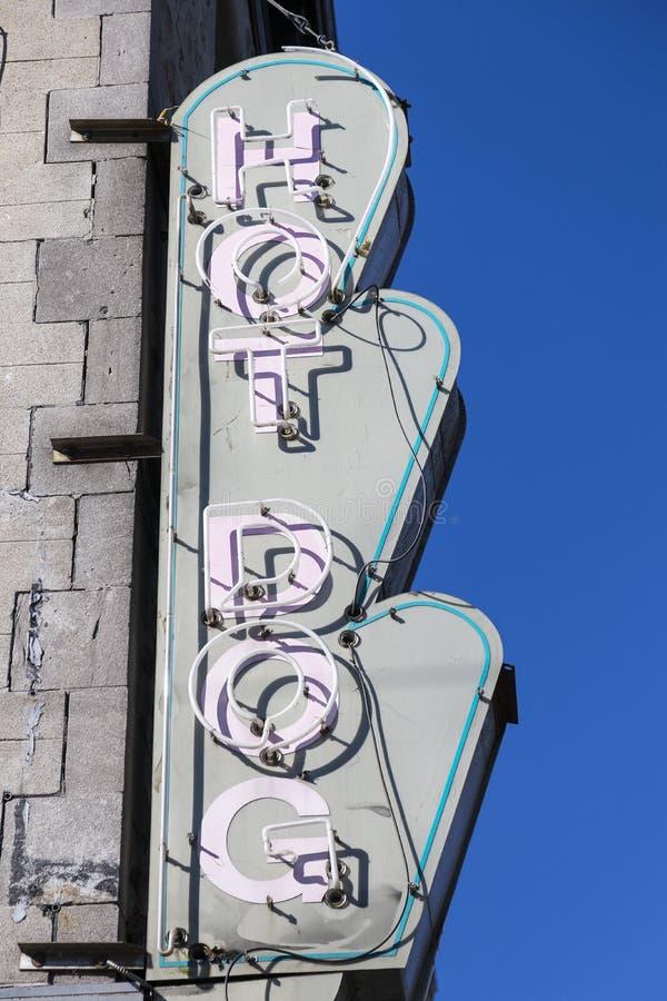 La foto vertical del perrito caliente del vintage horneó la muestra a la crema y con pan rallado en lado del edificio de piedra fotografía de archivo libre de regalías