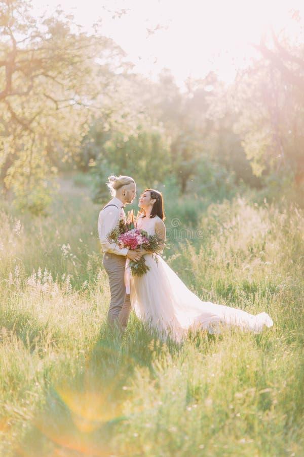 La foto vertical preciosa de los pares del recién casado que se detienen en el fondo del campo soleado imagen de archivo libre de regalías