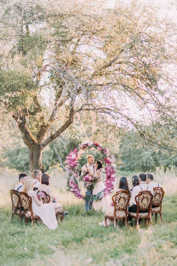 La foto verticale della cerimonia di nozze disposta nel legno soleggiato La coppia della persona appena sposata sta stando dietro fotografia stock