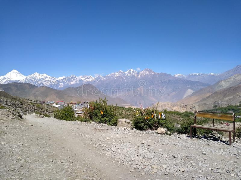 La fotografía o el contexto del estudio, el banco vacío en primero plano, Dhaulagiri e Himalaya hielo-capsularon las montañas en  imagen de archivo libre de regalías