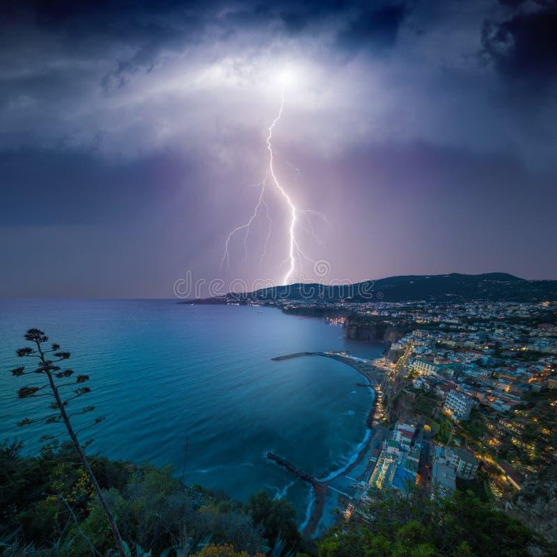 La foudre énorme du ciel orageux foncé heurte la ville côtière image stock