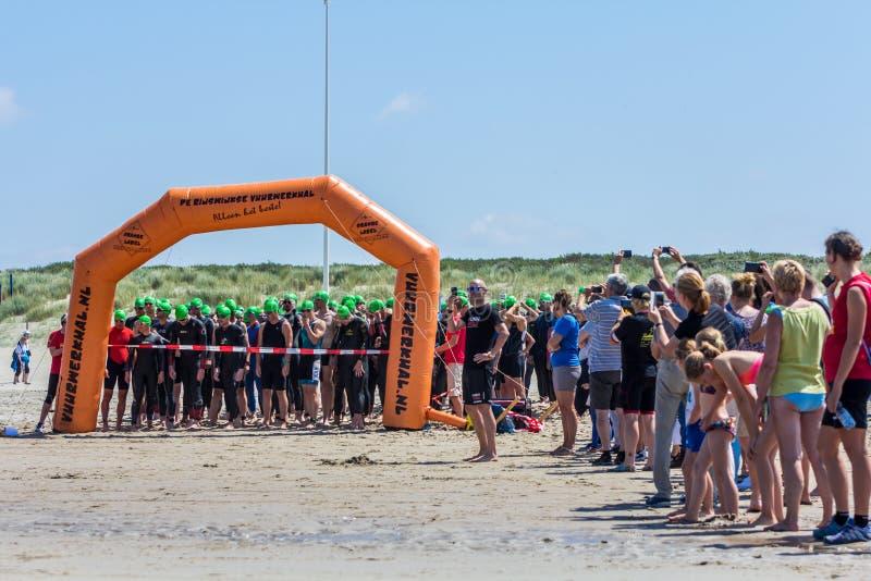 La foule et les athlètes se réunissent à la ligne de début de triathlon de croix de Kijkduin photos libres de droits