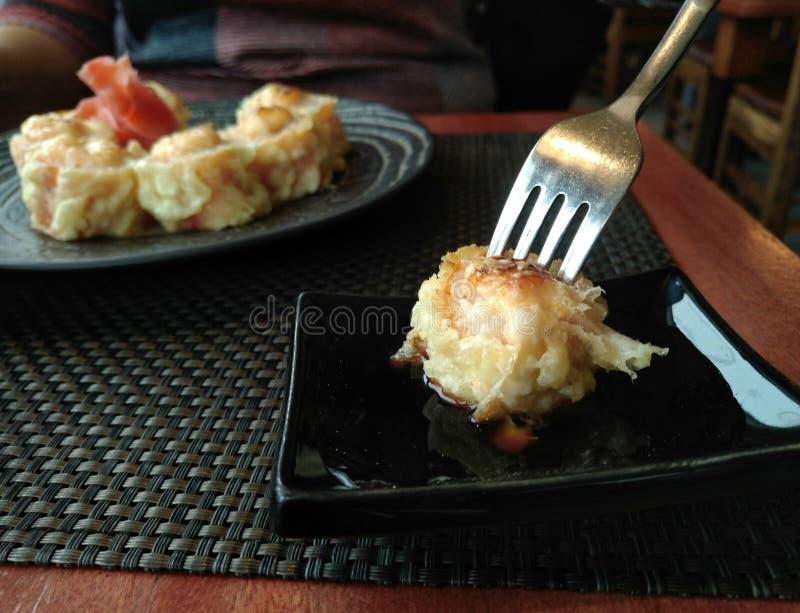 La fourchette avec le petit pain a plongé en sauce de soja image libre de droits