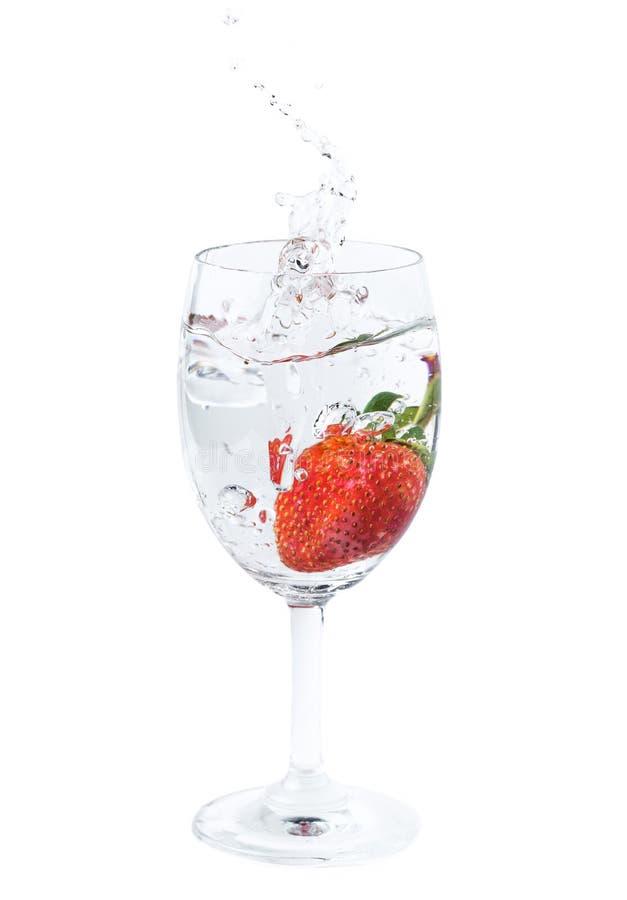 La fragola fresca è caduto nell'acqua in vetro di vino con spruzzata fotografia stock libera da diritti