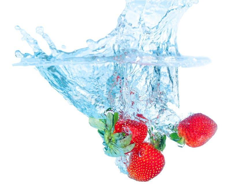 La fraise fraîche a relâché dans l'eau avec l'éclaboussure photos libres de droits