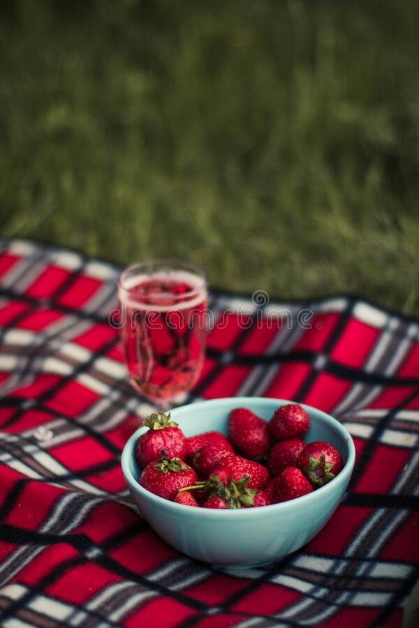 La fraise sur le bol rond blanc en céramique sur le textile rose blanc et brun photo libre de droits