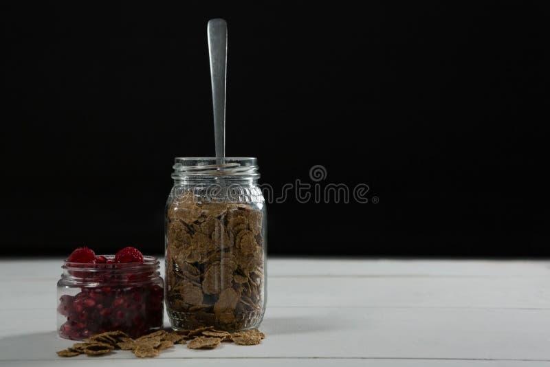 La framboise et le blé s'écaille dans le pot en verre images libres de droits