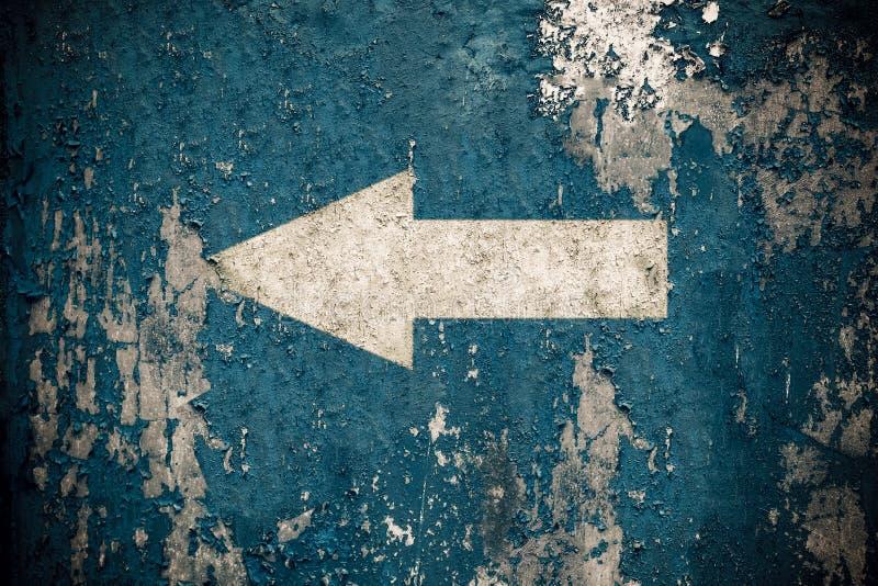 La freccia bianca dipinta sul vecchio lerciume e la parete blu stagionata strutturano il fondo immagine stock libera da diritti