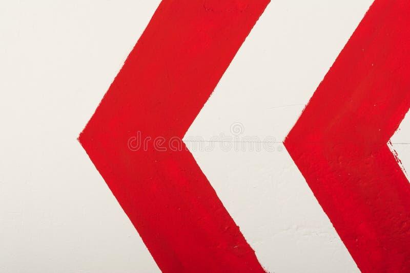 La freccia rossa indica la direzione a sinistra dipinta con pittura su una parete bianca fotografie stock libere da diritti