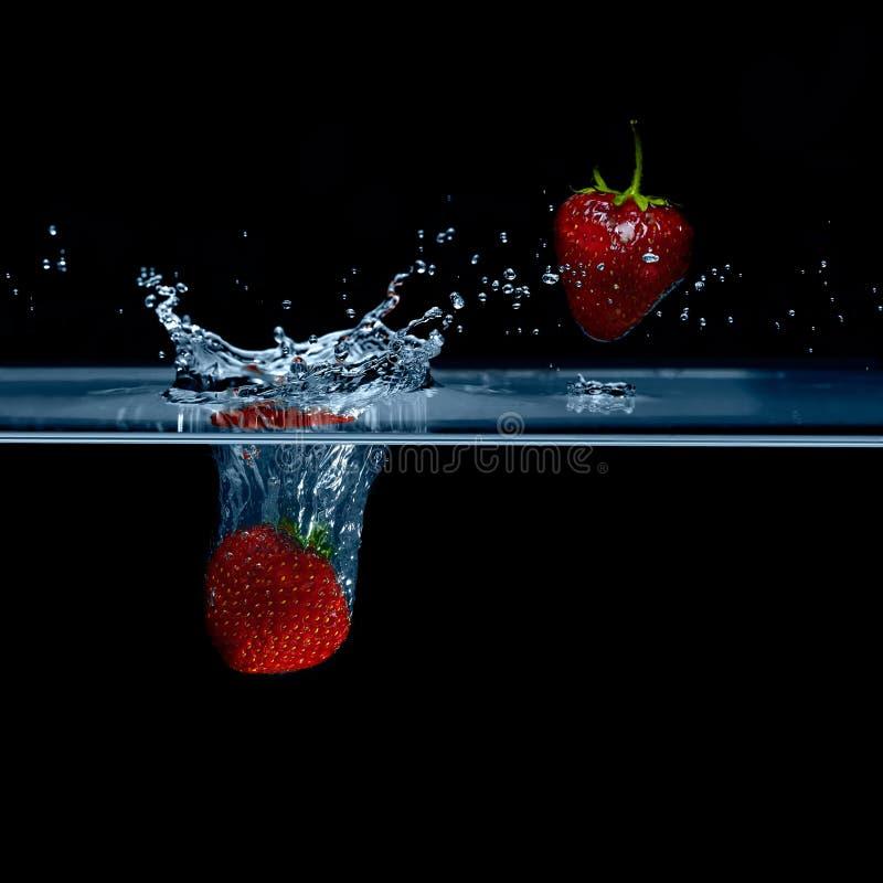 La fresa cae en el agua Fresas en el aire Wat del chapoteo foto de archivo