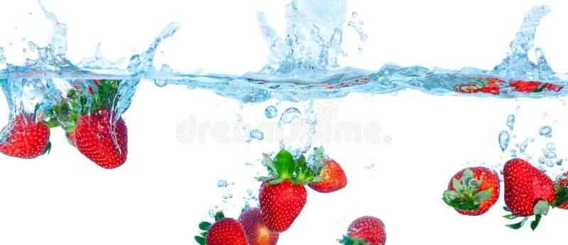La fresa cayó en el agua imagen de archivo