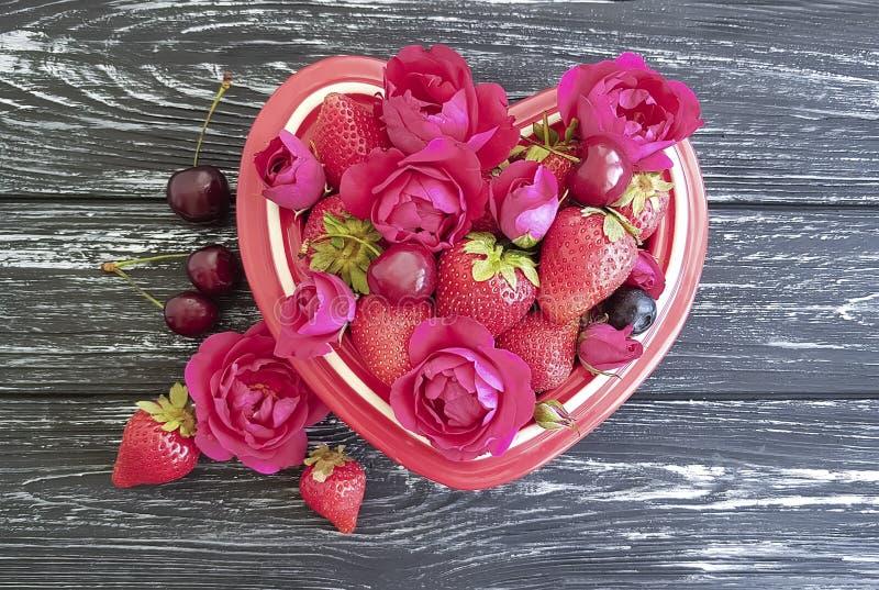 La fresa, cereza, corazón natural de la placa de la fruta del arándano, flor apetitosa del vintage fresco subió en un fondo de ma foto de archivo