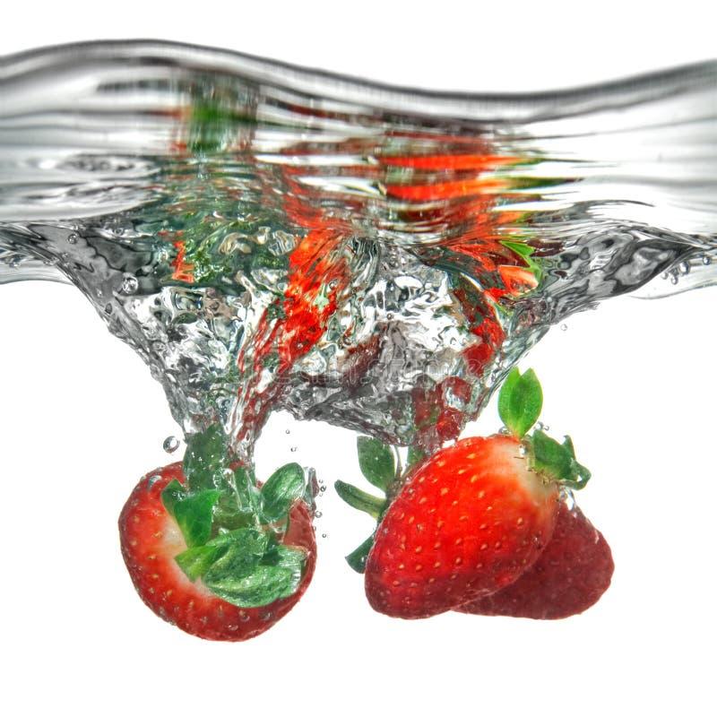 La fresa fresca cayó en el agua con el chapoteo imagenes de archivo