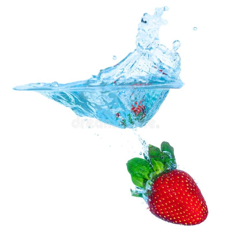 La fresa fresca cayó en el agua con el chapoteo imágenes de archivo libres de regalías