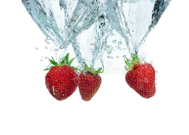 La fresa fresca cayó en el agua con el chapoteo fotos de archivo