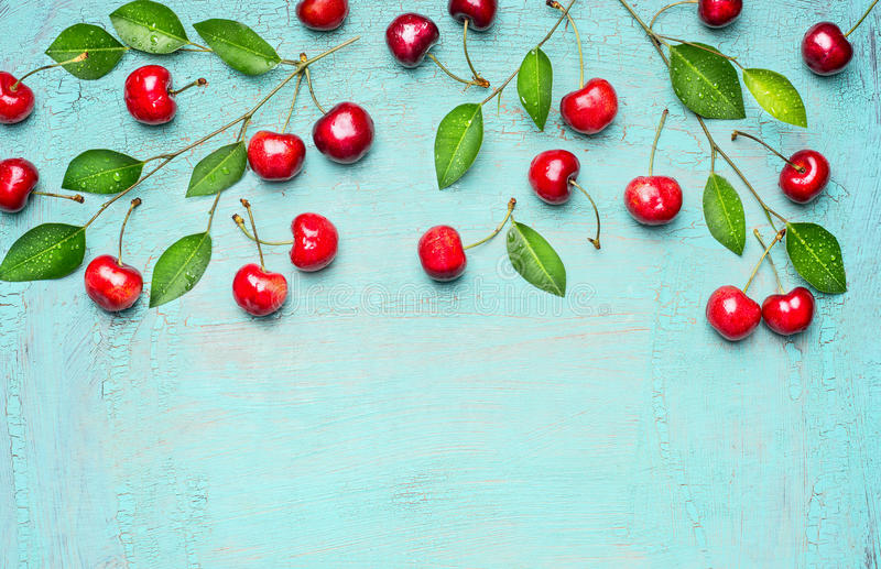 La frontera de cerezas dulces en rama con verde se va en el fondo azul claro, visión superior, lugar para el texto imagen de archivo libre de regalías