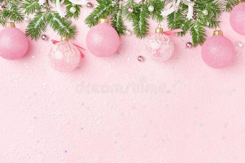 La frontera de la Navidad del Año Nuevo adorna el abeto en fondo rosado imagen de archivo