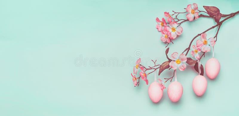 La frontera de Pascua con el colgante de los huevos de Pascua del rosa en colores pastel y la primavera florecen en la luz en el  fotos de archivo