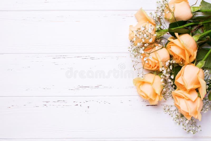 La frontera de rosas del color del melocotón florece en el fondo de madera blanco fotografía de archivo