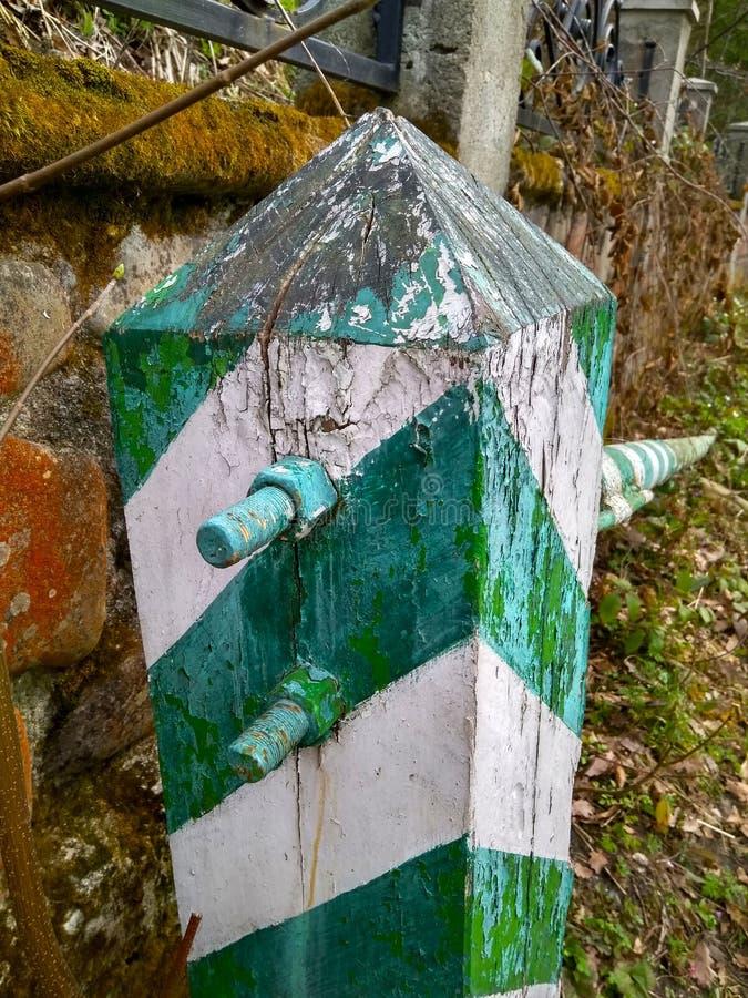 La frontera vieja rayó blanco con una barrera verde en el bosque imagen de archivo libre de regalías