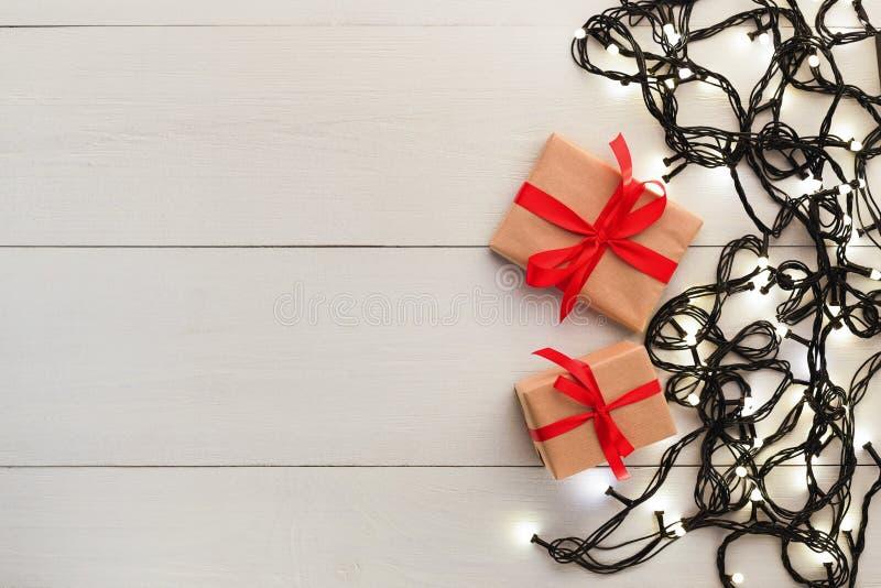 La frontière des cadeaux et de la guirlande s'allume sur le fond en bois image libre de droits