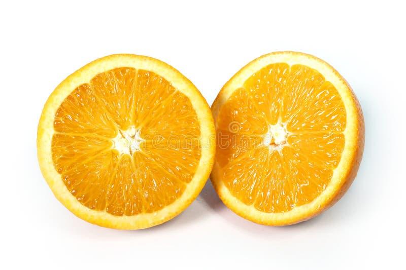 La fruta anaranjada fresca y sana partida en dos aisló blanco imagenes de archivo
