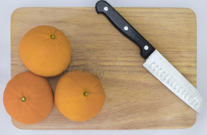La fruta anaranjada se coloca en un piso de madera con una opinión de top hermosa del cuchillo fotografía de archivo