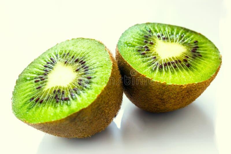 La fruta de kiwi cortó en dos pedazos contra un fondo ligero fotografía de archivo libre de regalías