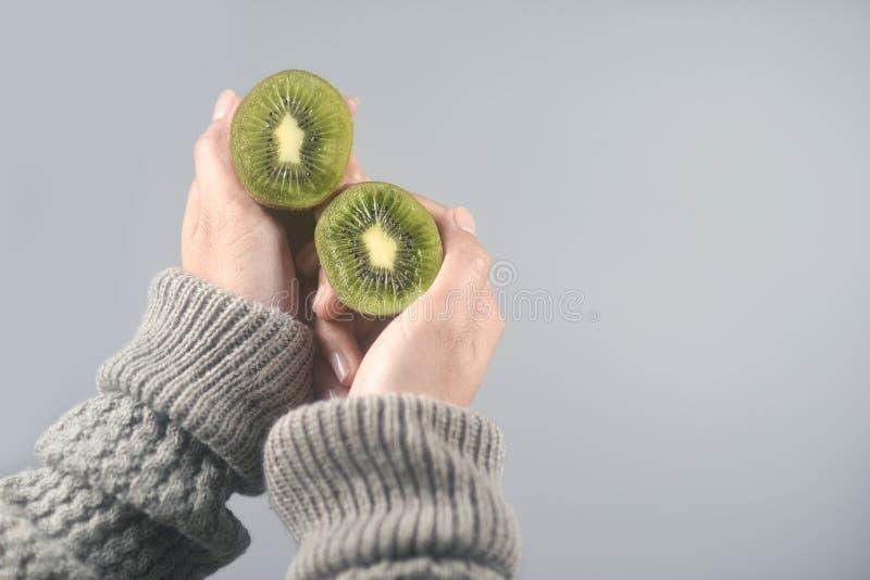 La fruta de kiwi, mitad cortó 2 pedazos en las manos de las mujeres con el suéter en fondo gris claro Imagen horizontal foto de archivo
