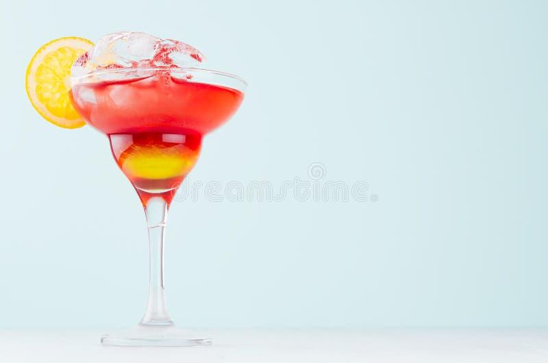 La fruta fresca del verano acod? el c?ctel rojo, amarillo de la salida del sol con la rebanada anaranjada, cubos de hielo en copa fotografía de archivo