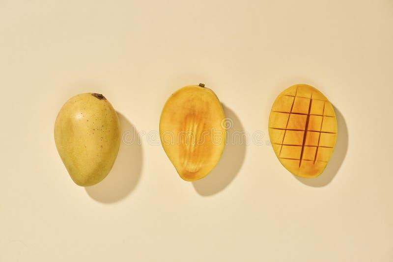 La fruta fresca y hermosa del mango con los pedazos cortados en cuadritos cortados del mango en el fondo en colores pastel, espac fotos de archivo