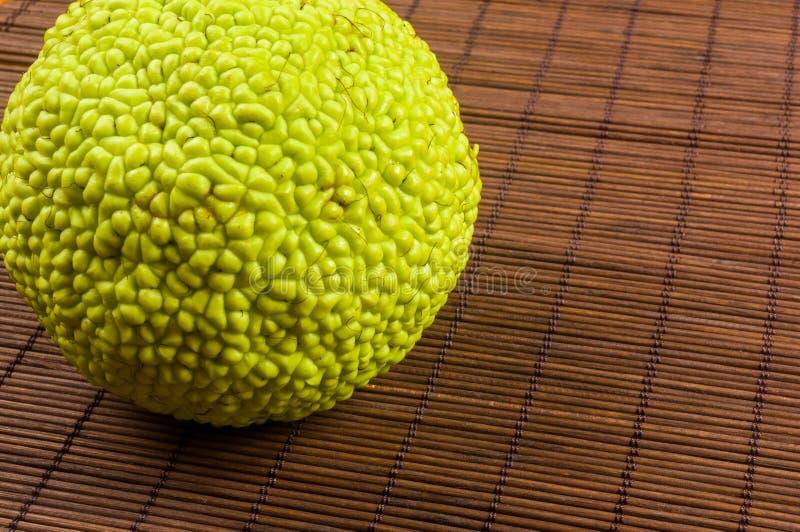 La fruta verde del pomifera del maclura, naranja de osage, manzana del caballo, nuez de Adán crece en la estera de bambú fotos de archivo libres de regalías
