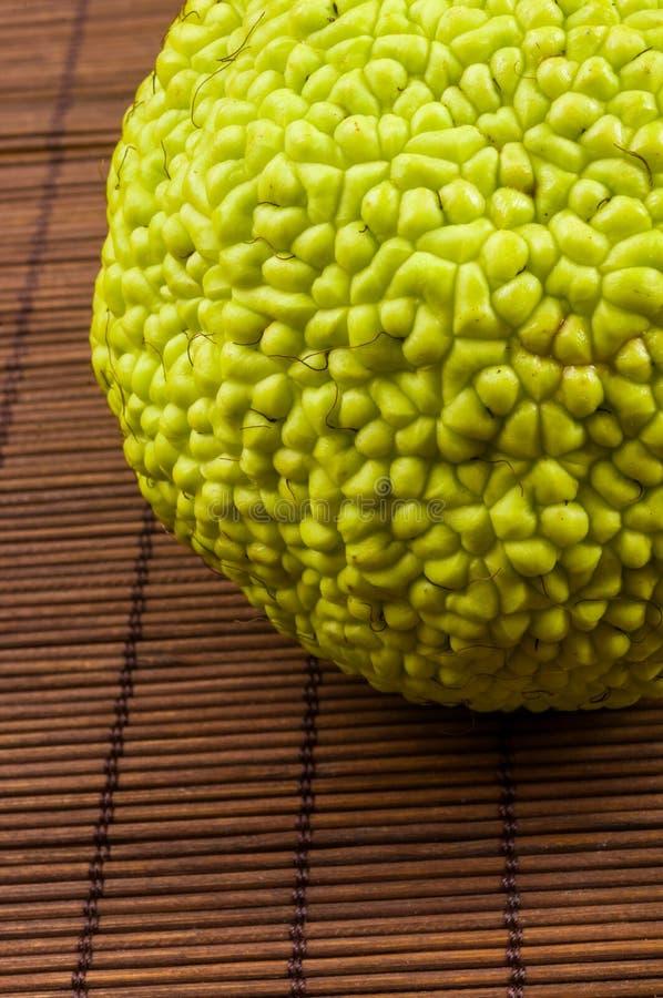 La fruta verde del pomifera del maclura, naranja de osage, manzana del caballo, nuez de Adán crece en la estera de bambú fotografía de archivo libre de regalías