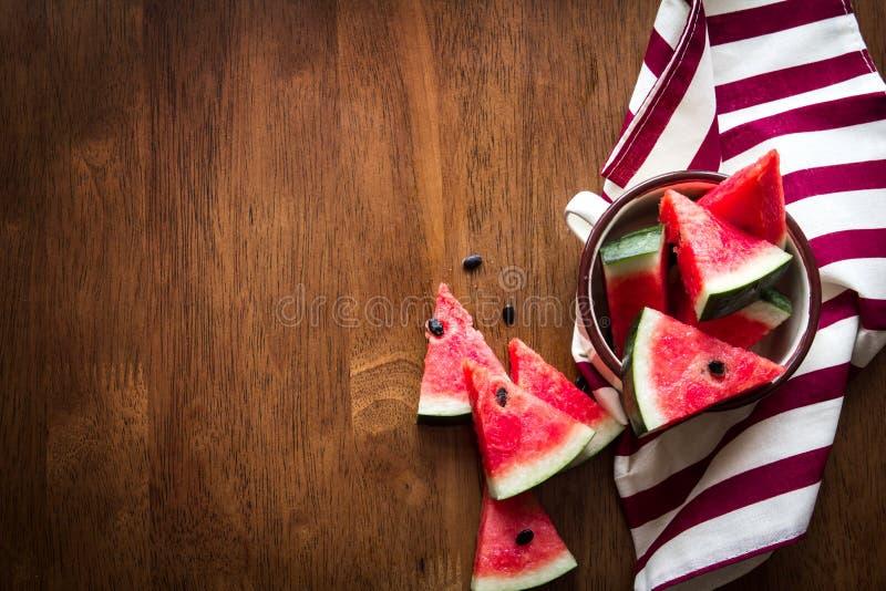 La frutta affettata fresca dell'anguria su fondo di legno marrone, completa la a immagini stock