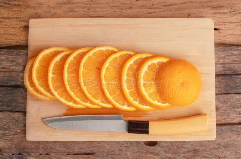 La frutta arancio ha affettato ed il coltello sul tagliere fotografia stock libera da diritti
