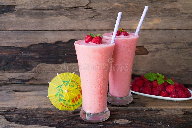 La frutta dei frullati yogurt, del succo e del lampone del lampone per perdita di peso beve su un fondo di legno immagine stock