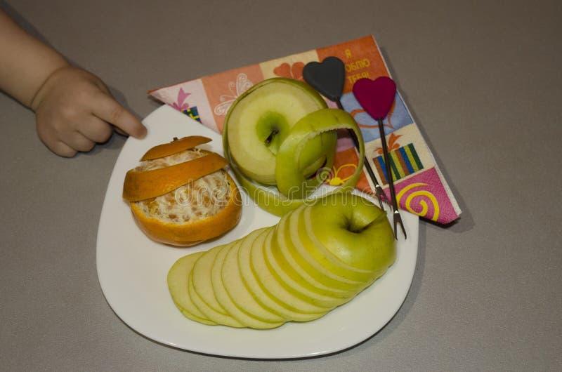 La frutta del taglio su un'arancia della mela del piatto la maniglia del ` s del bambino immagini stock libere da diritti