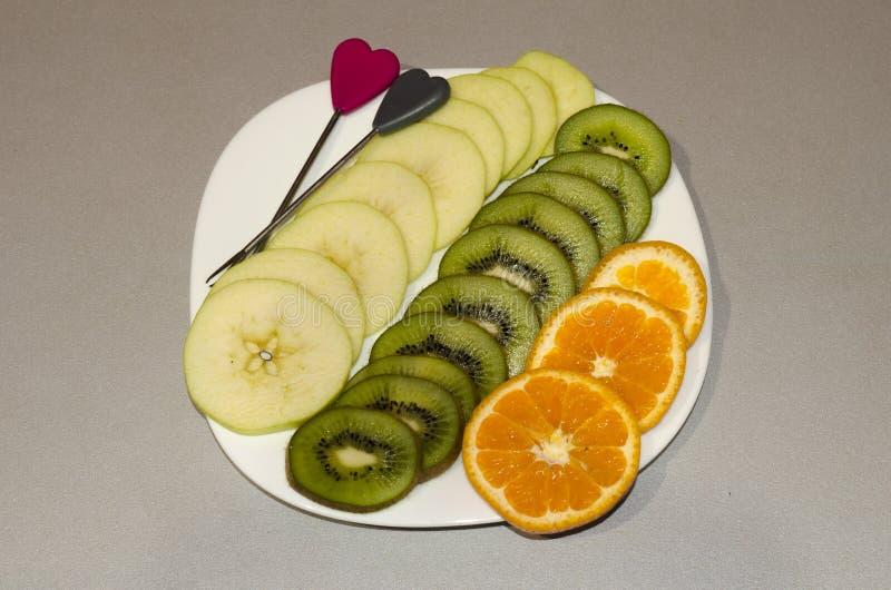 La frutta del taglio su un taglio arancio della mela del piatto dai segmenti immagine stock