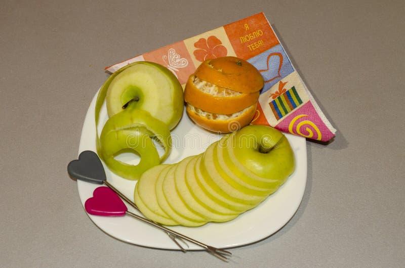 La frutta del taglio su un taglio arancio della mela del piatto dai segmenti fotografia stock