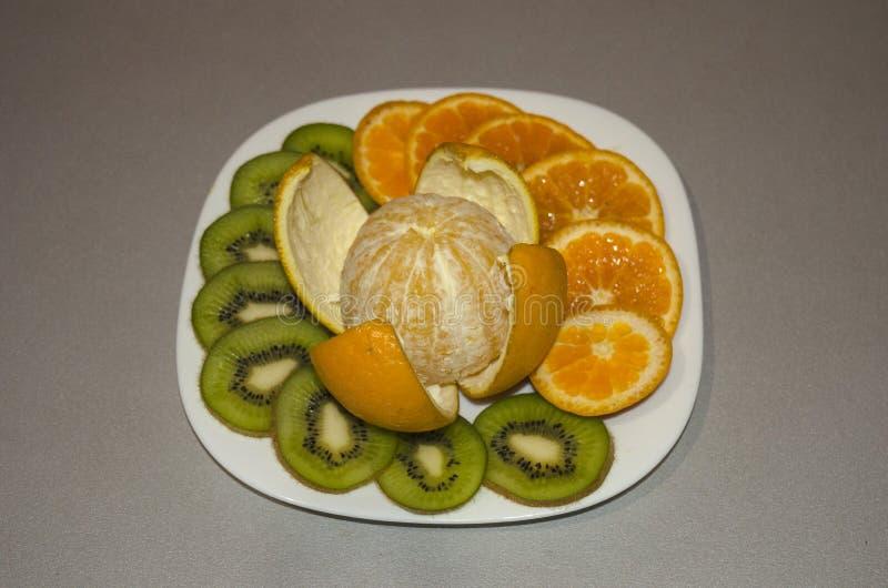 La frutta del taglio su un taglio arancio della mela del piatto dai segmenti fotografie stock