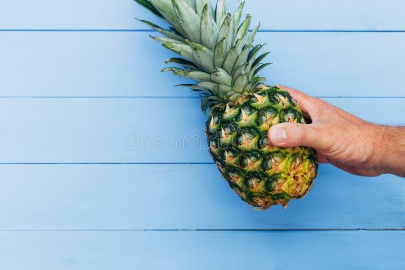 La frutta dell'ananas ha tenuto a disposizione su fondo di legno blu immagine stock libera da diritti