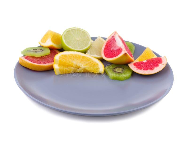 La frutta tropicale riempie la metà giusta di un piatto su un fondo isolato bianco immagine stock libera da diritti