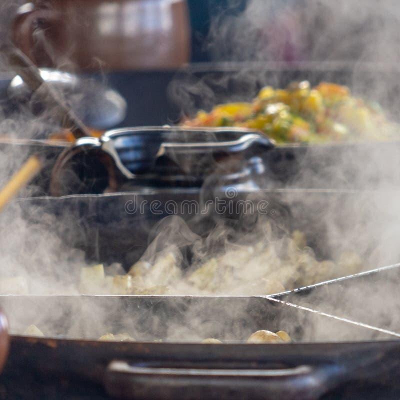 La fucilazione dei vulcanizzatori a vapore grandi, vapore nella priorità alta messa a fuoco, pentola di verdure nei precedenti ha immagine stock