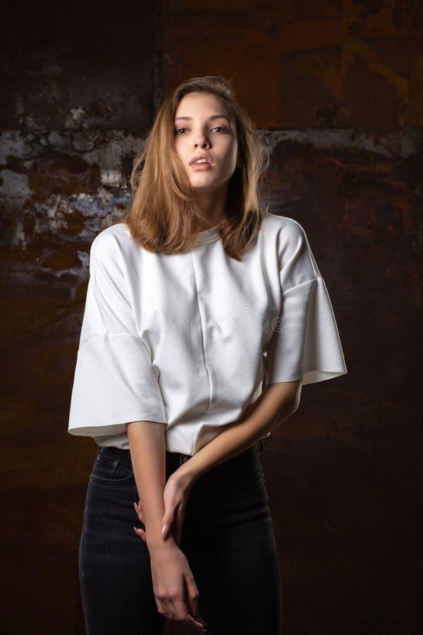 La fucilazione della prova per il modello giovane seducente porta i jeans e la camicia immagine stock