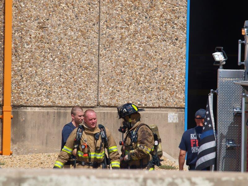 La fumée, la chaleur et l'humidité lourde s'ajoutent aux soucis de sécurité pour des pompiers images stock