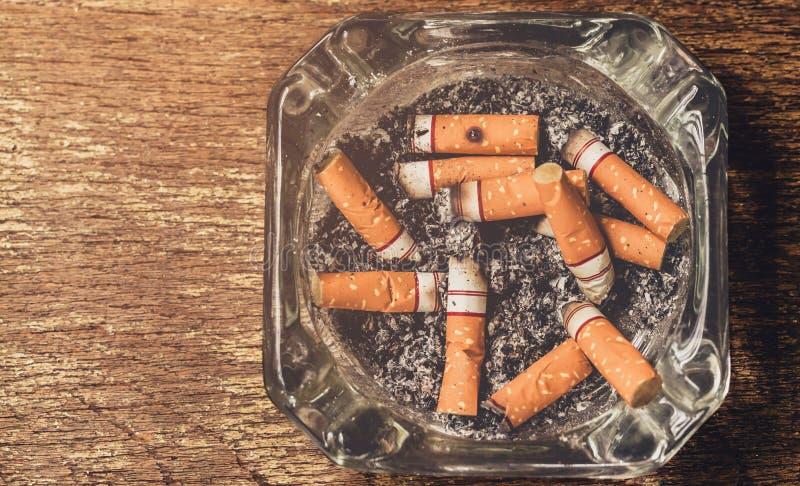 La fumée de cigarette est alors les cigarettes jetées image libre de droits