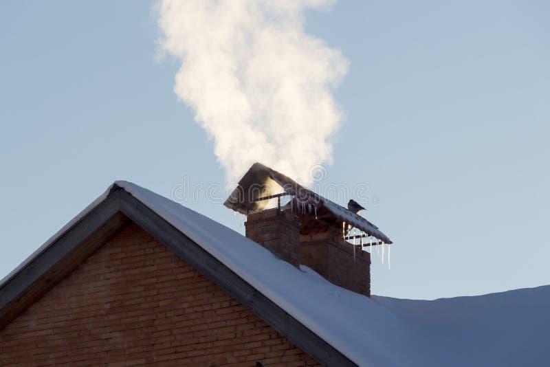 La fumée de la cheminée d'une maison privée photo libre de droits