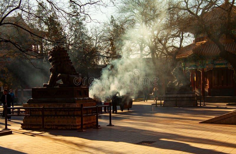 La fum?e des visiteurs br?lent l'encens par les statues chinoises de lion de gardien dans le temple de Yonghegong, Lama Temple, d photos stock