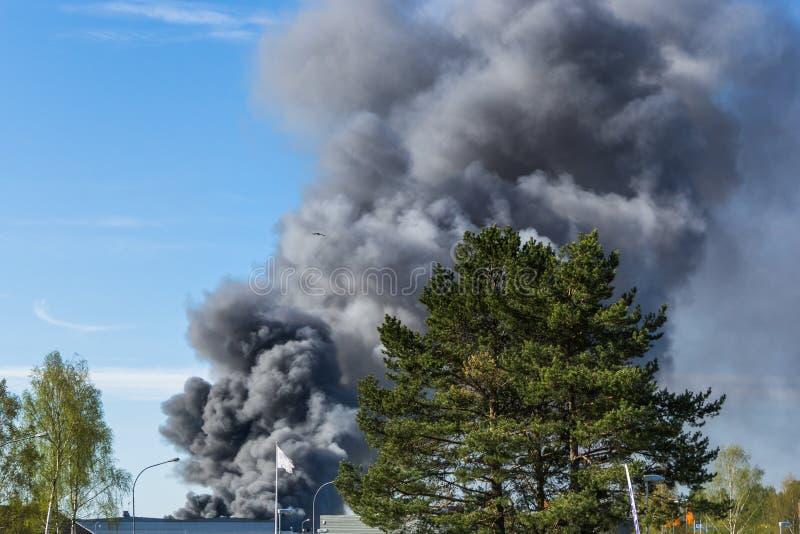 La fumée noire épaisse du feu se lève au ciel image stock