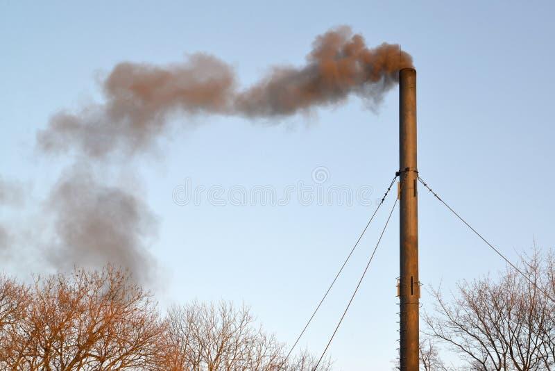La fumée noire d'un tuyau d'une chaufferie de charbon pollue l'air photographie stock